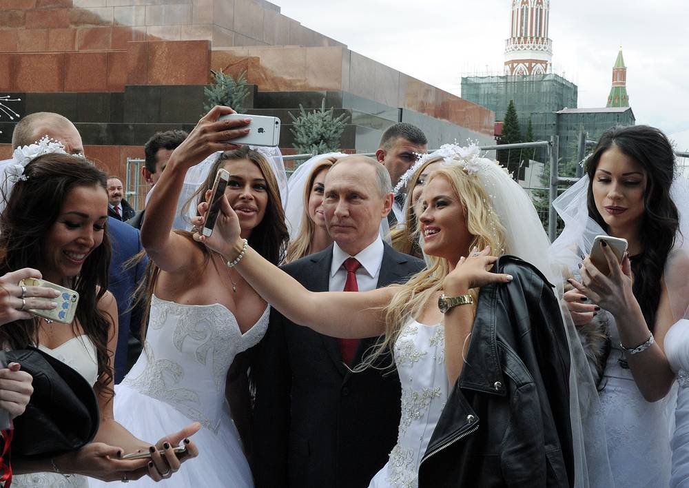 Russia's President Vladimir Putin poses for selfies with brides at the opening of Moscow City Day in the Red Square