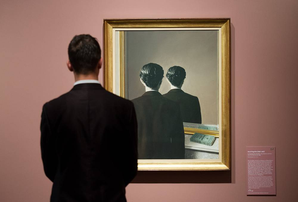 A man looks at the work 'Not to be Reproduced' by Rene Magritte at the Kunsthalle art gallery in Hamburg, Germany, October 5