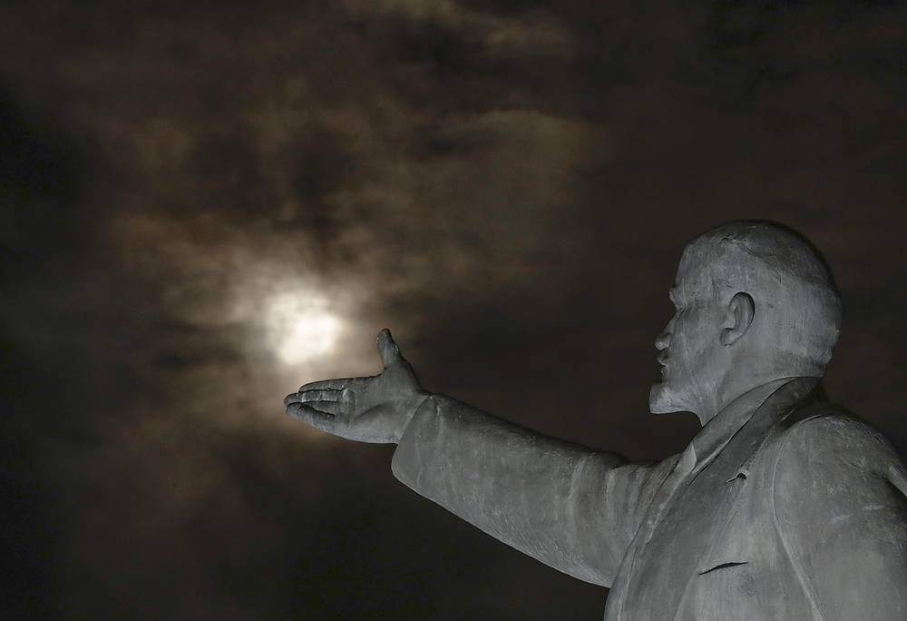 The super moon rises through the clouds over a statue of Soviet Union founder Vladimir Lenin at Baikonur cosmodrome, Kazakhstan, November 14