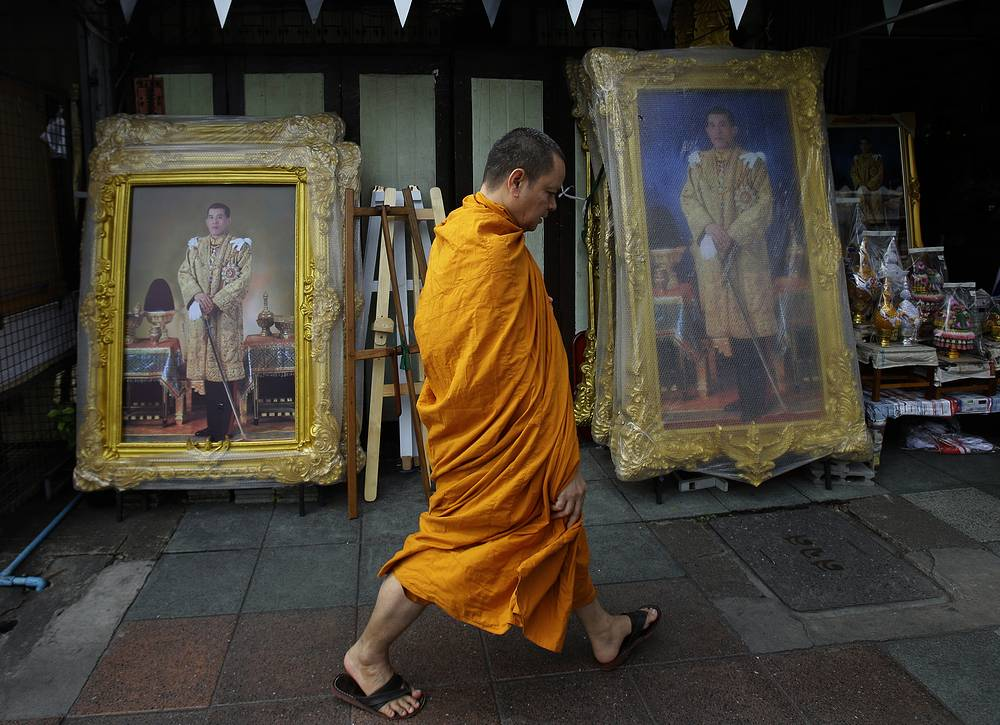 A Thai Buddhist monk walking past portraits of Thailand's newly appointed King Maha Vajiralongkorn Bodindradebayavarangkun in Bangkok, December 2