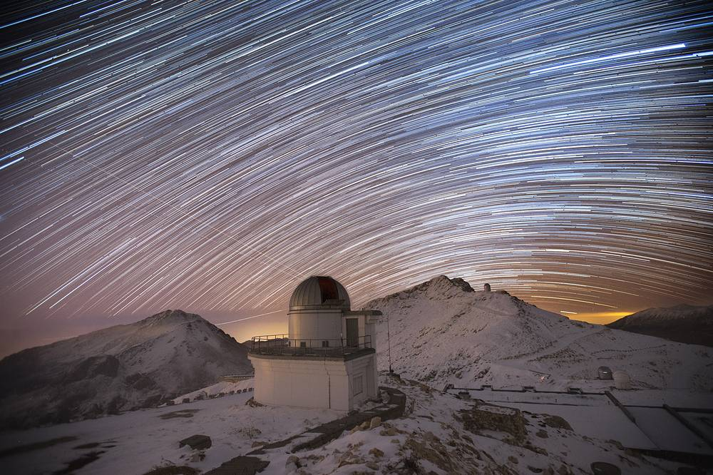 A long exposure image of a night sky and the building of the T60 telescope at the TUBITAK National Observatory in Antalya