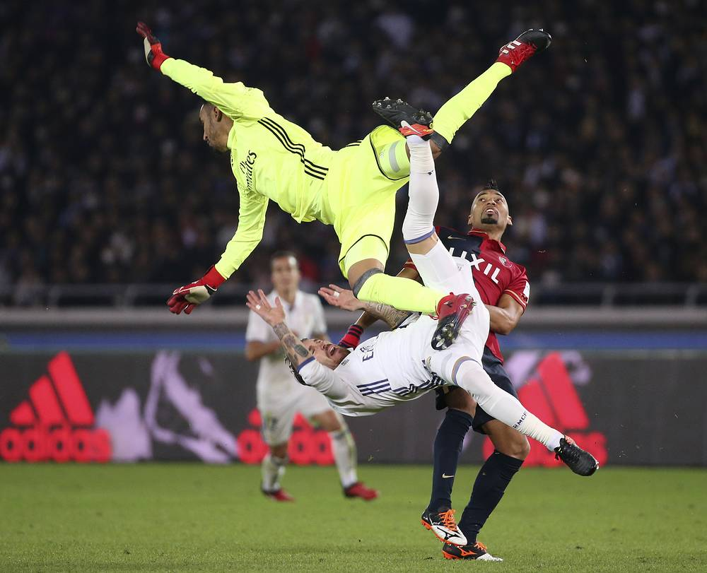Kashima Antlers' Fabricio collides with Real Madrid's Sergio Ramos and goalkeeper Keylor Navas for a ball battle during their final match at the FIFA Club World Cup soccer tournament in Yokohama, Japan, December 18
