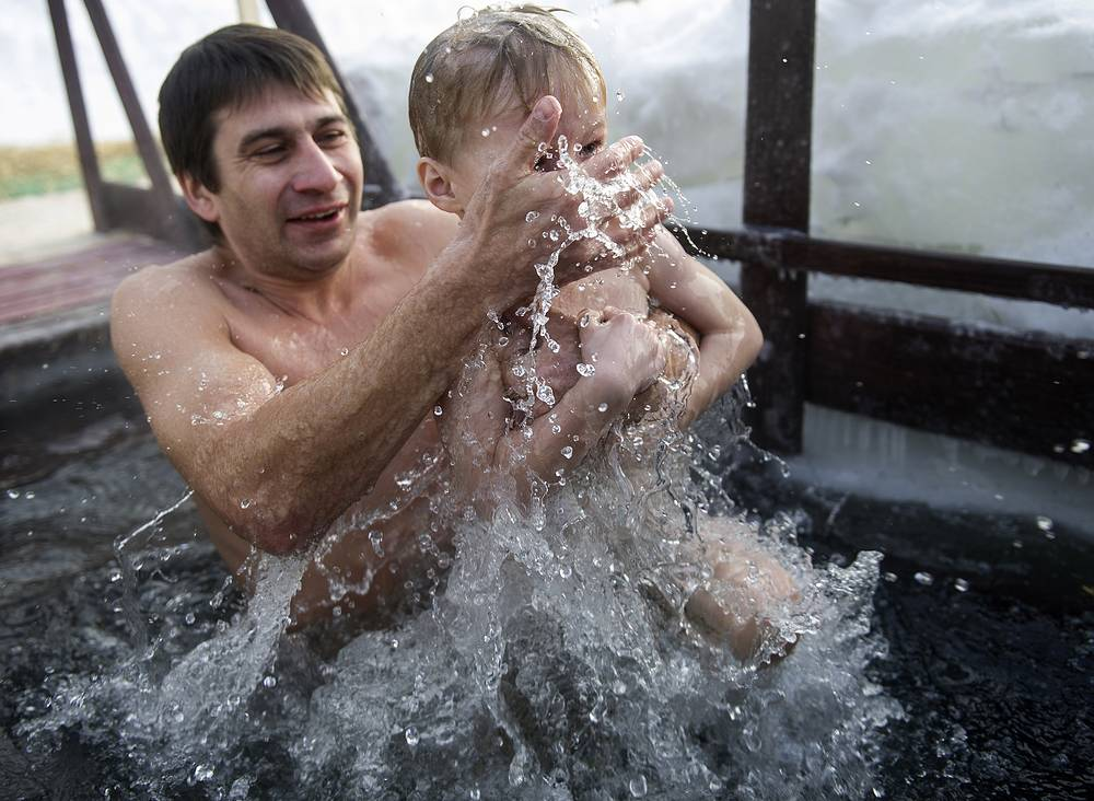 A man with a child dips in the icy waters of the Ob River during the celebration of Epiphany in Novosibirsk