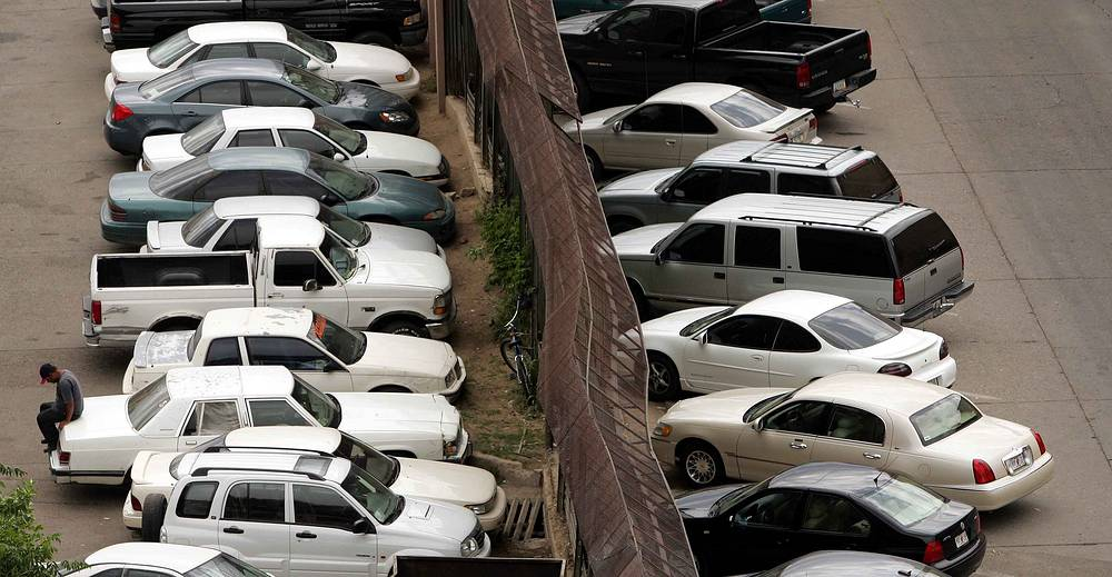 Сars parked in Nogales, Mexico, on one side of the metal wall that divides Nogales, Mexico, from Nogales, Arizona, as other cars sit parked on the US side, 2006