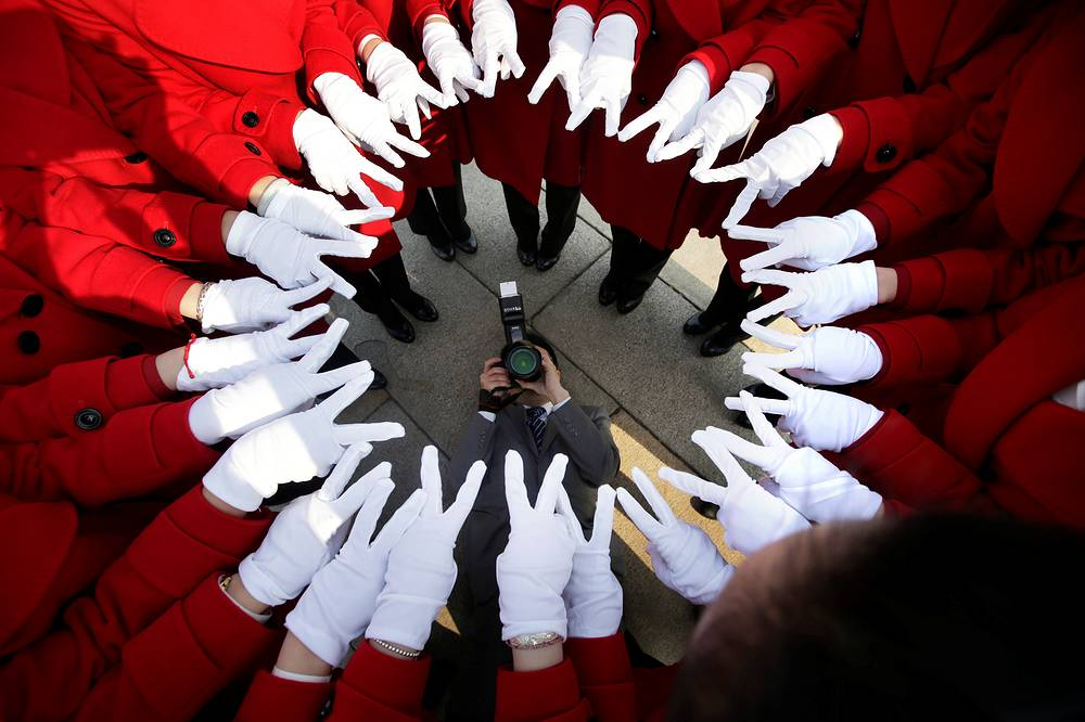 Attendants serving delegates from a hotel pose for a photo at Tiananmen Square as delegates attend a meeting during the annual session of China's parliament, the National People's Congress in Beijing, China, March 4
