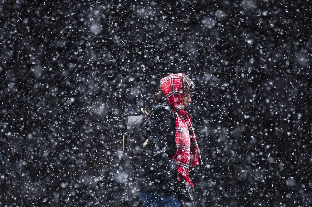 A woman walks through a winter snow storm in Philadelphia