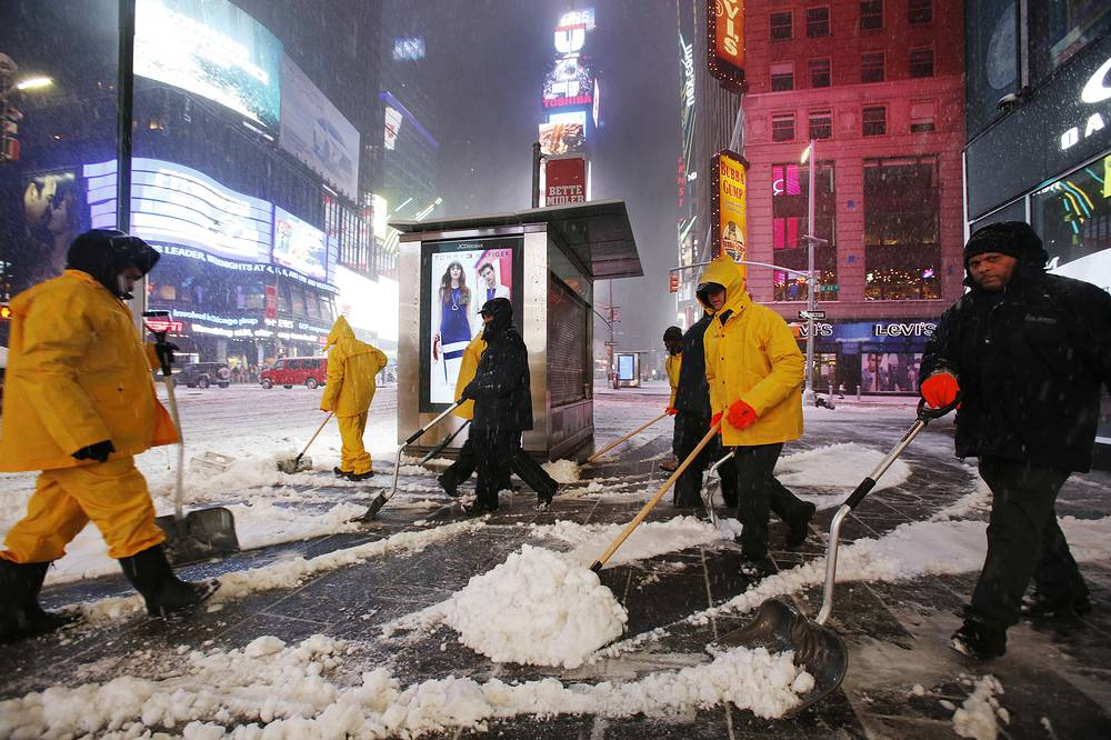 A crew of snow shovelers work as a snowstorm sweeps through Times Square, in New York