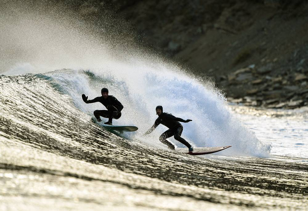 People surfing in Chernyshev Bay off Russky Island, on the south-east Pacific coast of Russia, April 30
