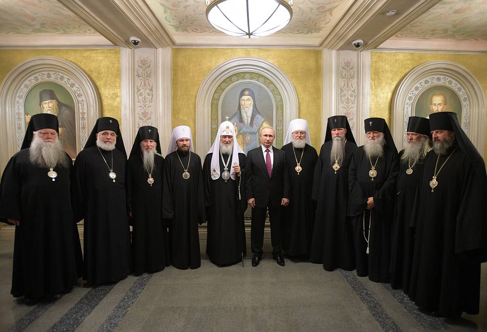 Metropolitan Hilarion of Volokolamsk, Patriarch Kirill of Moscow and all Russia and Russia's President Vladimir Putin pose for a photograph with representatives of the Russian Orthodox Church Abroad at the Sretensky Monastery in Moscow, Russia, May 25