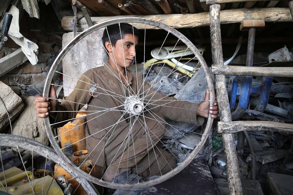 An Afghan boy works at a workshop on the International Children's Day, in Jalalabad, Afghanistan, June 1