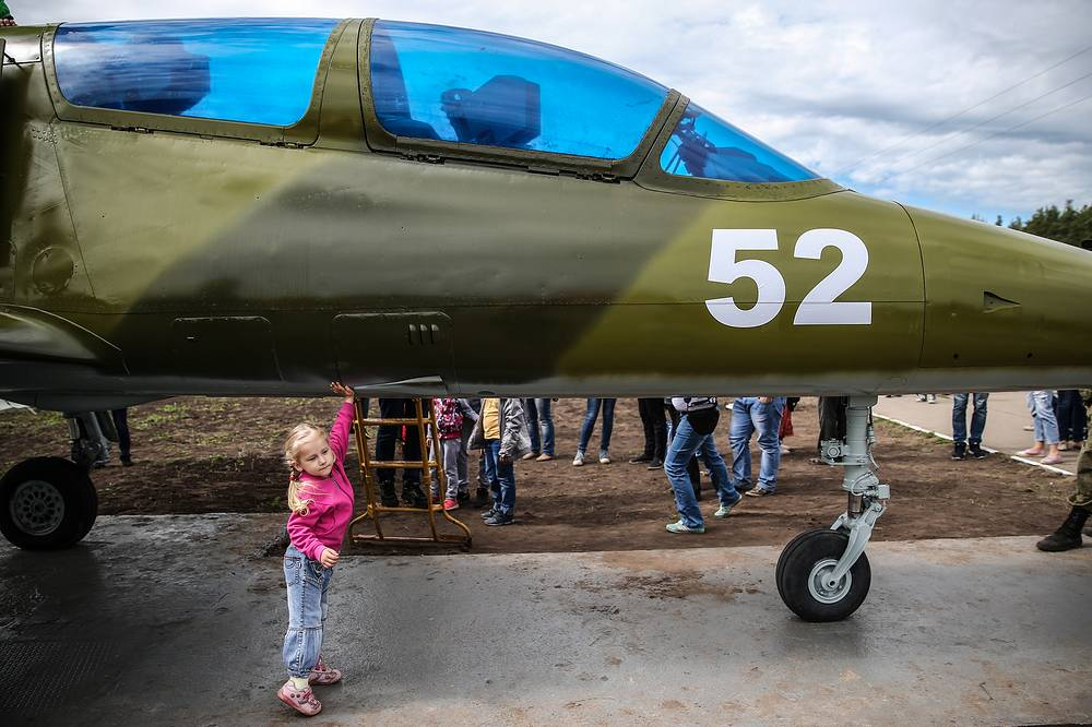 A child touches an aircraft during the Aviamix airshow, the opening event for the 2017 Aviadarts military aviation competition at the Pogonovo range, Voronezh region