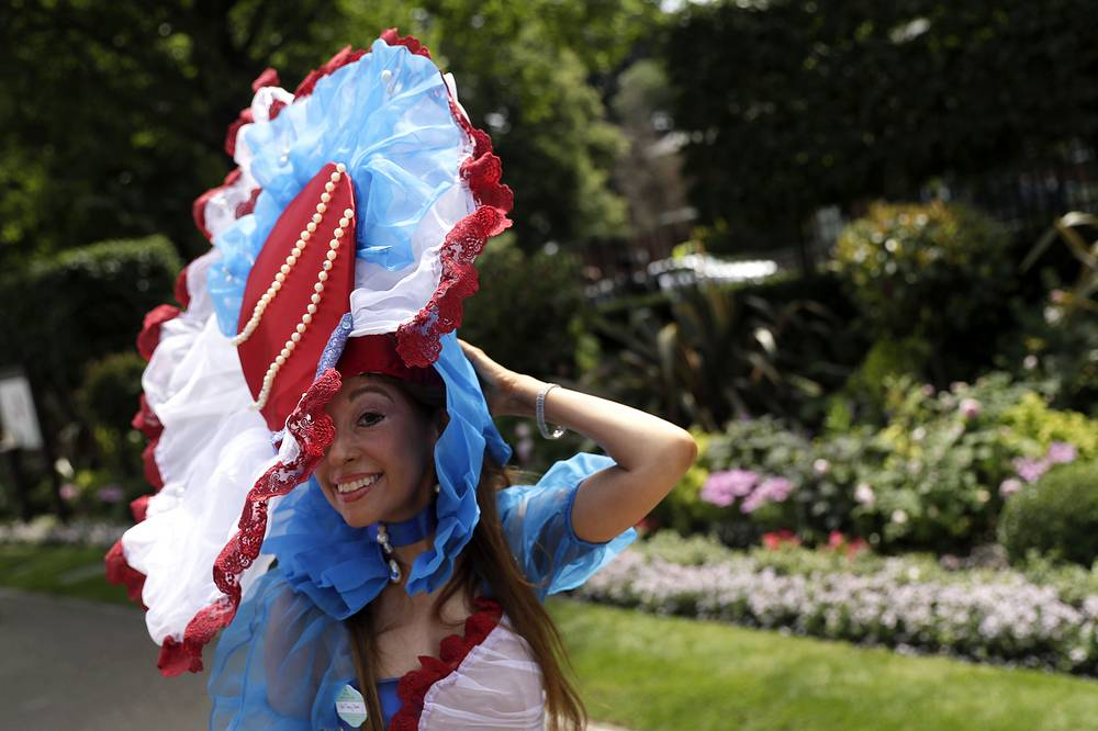 A racegoer poses for pictures