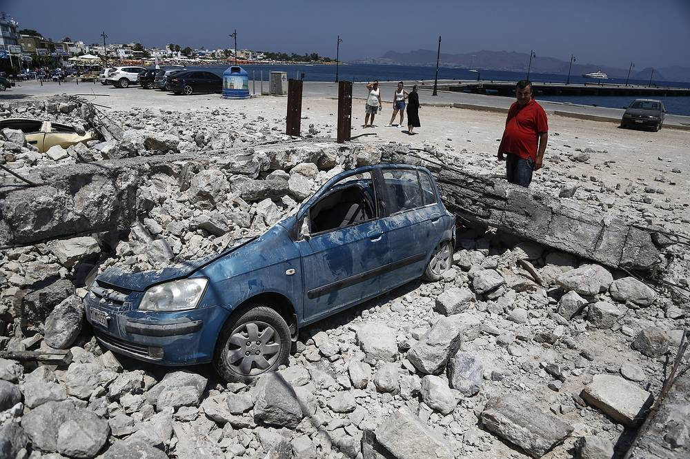 A man looks at a car crushed under rubble near the port, following an earthquake on the island of Kos, Greece, July 22