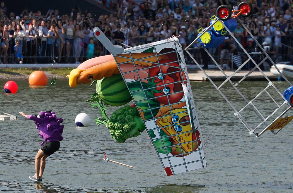 Participants dressed as vegetables jump into the water in their homemade flying machine