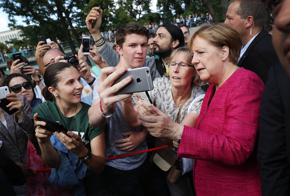 German Chancellor Angela Merkel pauses for a selfie among visitors during the annual open-house day at the Chancellery  in Berlin, Germany, August 27