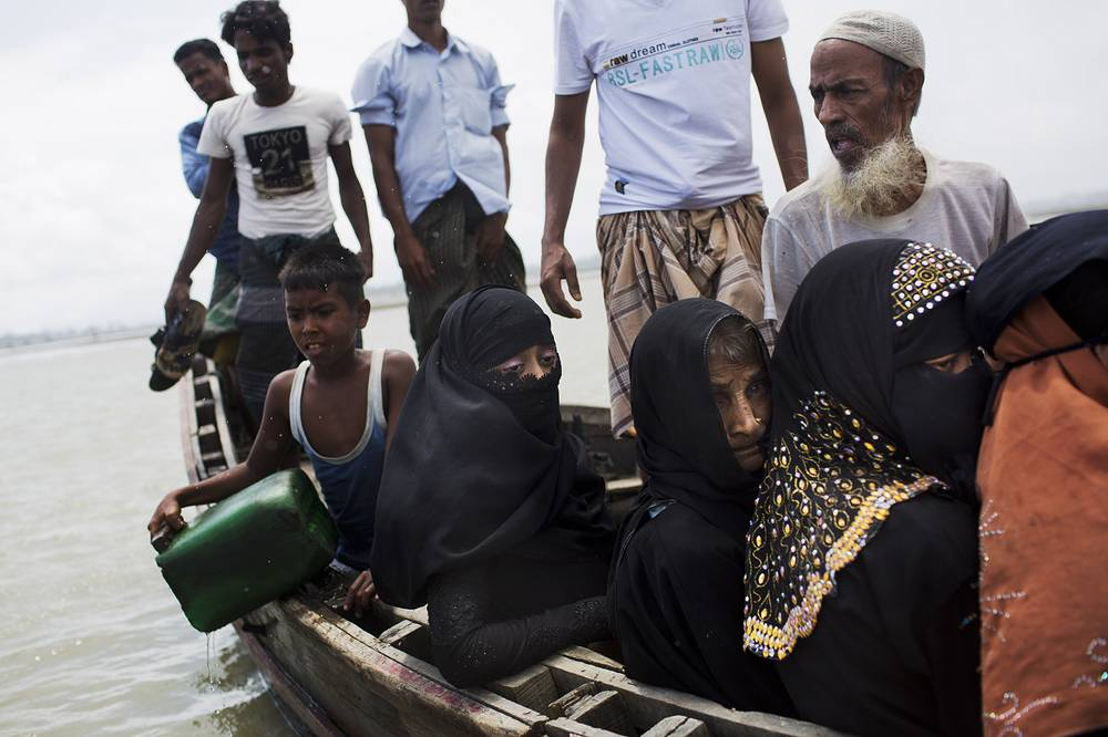Myanmar's Rohingya ethnic minority use a local boat to cross a stream after crossing over to the Bangladesh side of the border