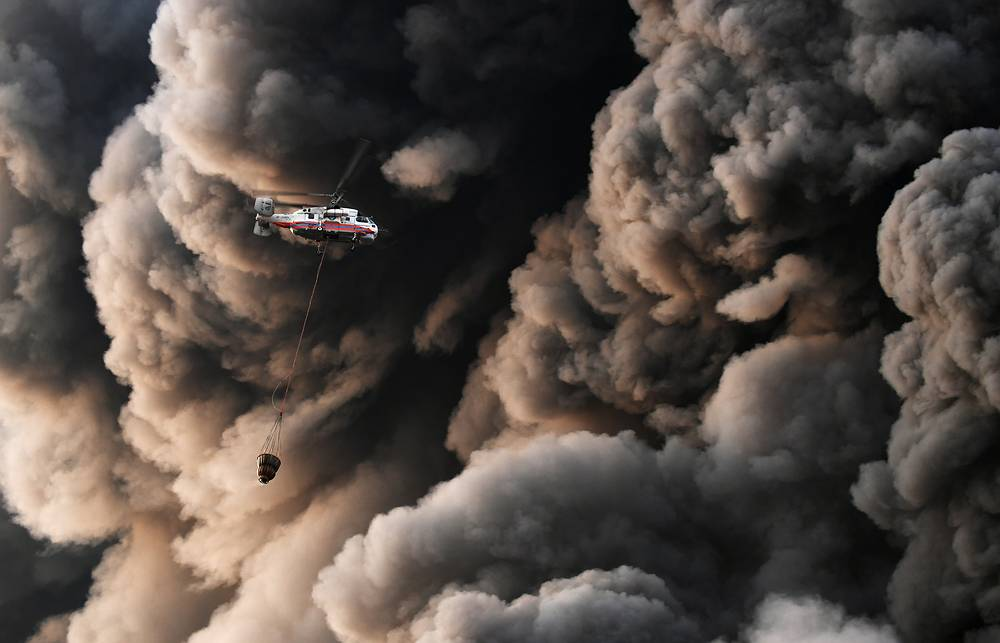 A Russian emergency service helicopter carries water past billows of smoke as fire fighters battle the blaze in Sindika, a shopping mall selling construction materials, at MKAD Moscow Ring Road on the western outskirts of Moscow, Russia, October 9