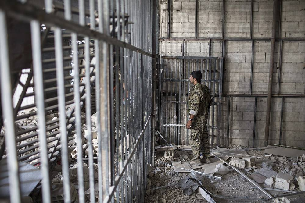 A members of the Syrian Democratic Forces walk inside a prison built by Islamic State fighters at the stadium in Raqqa