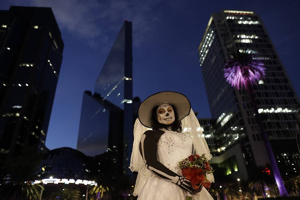 "A woman, dressed as a skeleton bride, poses for pictures during the Grand Procession of the ""Catrinas"" in Mexico City"