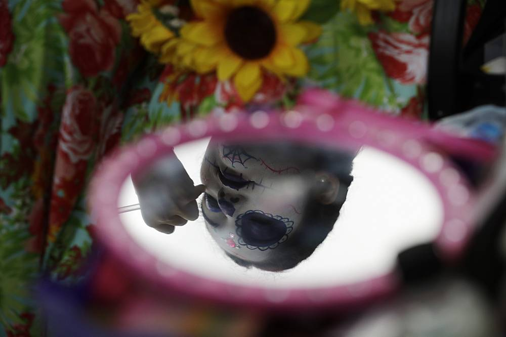"A young woman gets her face painted in the style of Mexico's iconic ""Catrina"""