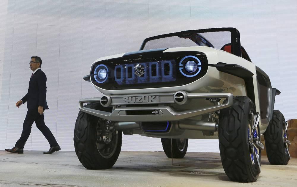 Toshihiro Suzuki, president of Suzuki Motor Corporation, walks by an e-SURVIVOR concept car at Suzuki's presentation