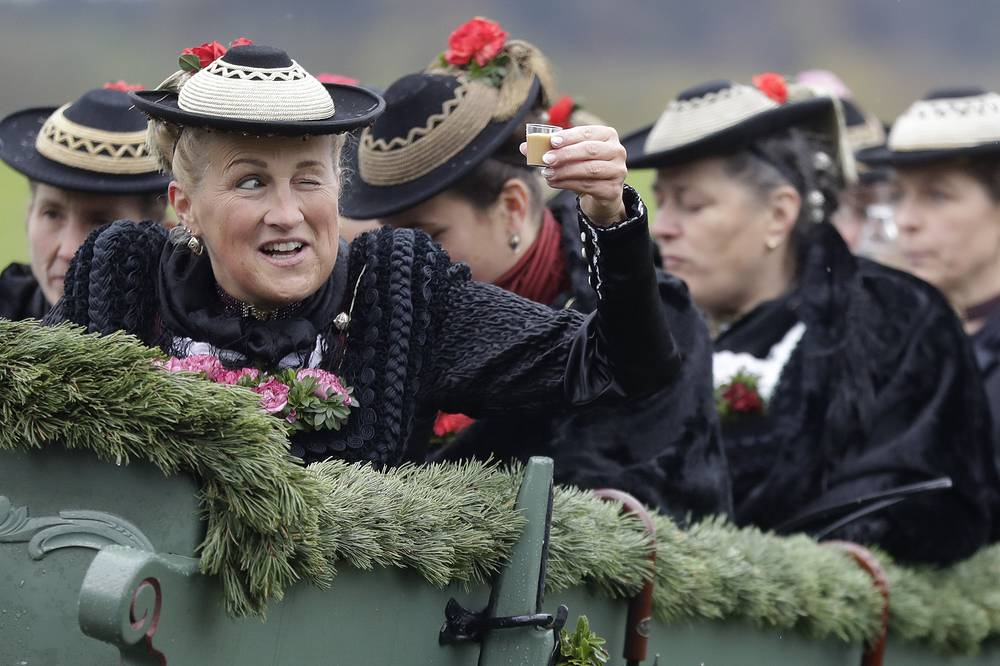 A woman in her costume of the region salutes with liqueur as she sits in a horse-drawn carriage during the traditional Leonhardi pilgrimage for horses and livestock in Warngau, Germany, October 22