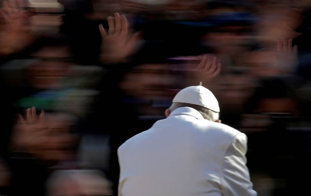 Pope Francis waves as he arrives to lead the Wednesday general audience in Saint Peter's square at the Vatican November 22