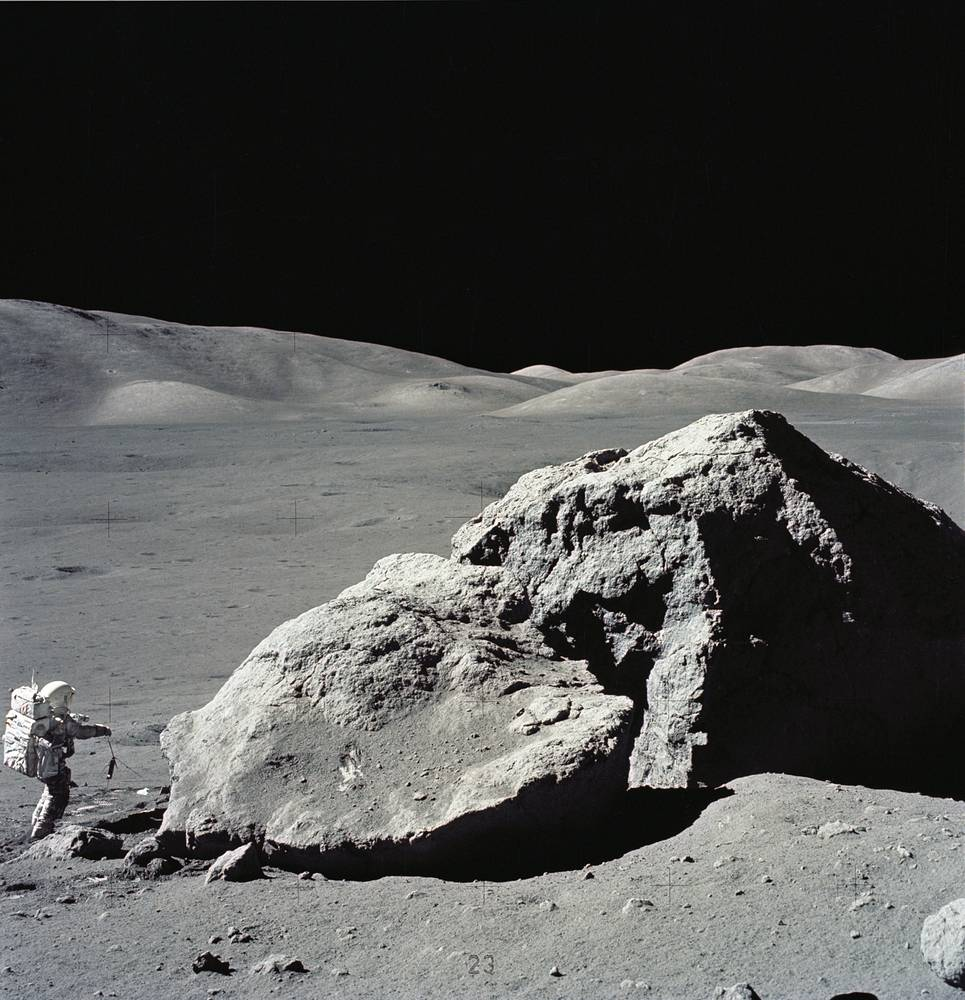 Astronaut Harrison H. Schmitt is photographed standing next to a huge, split boulder at the Taurus-Littrow landing site on the moon