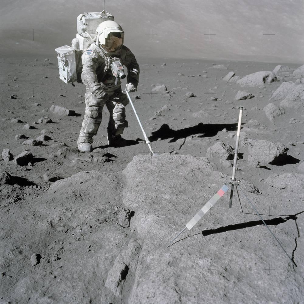 Scientist-astronaut Harrison Schmitt, Apollo 17 lunar module pilot, uses an adjustable sampling scoop to retrieve lunar samples at the Taurus-Littrow landing site on the moon