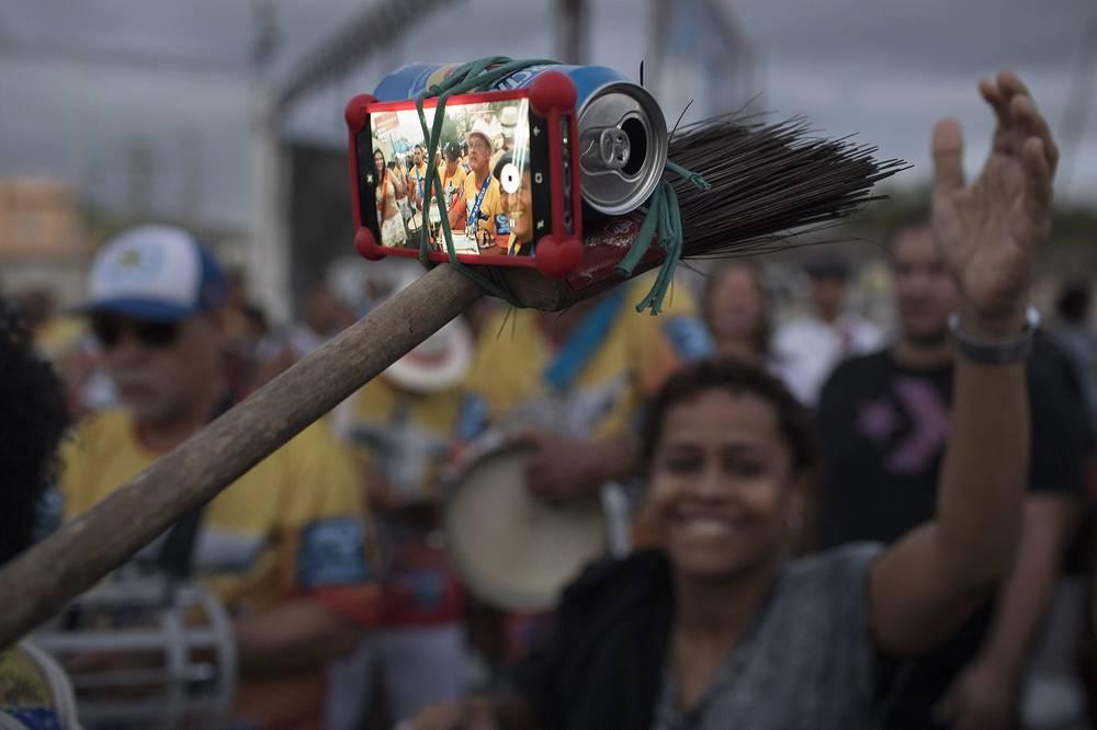 A samba band member turns a broom, beer can and rubber band into a selfie stick at the Oswaldo Cruz neighborhood, marking Samba Day, in Rio de Janeiro, Brazil, December 2