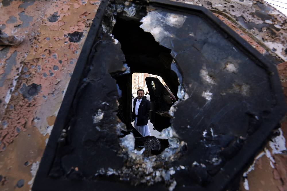 A Yemeni inspects a destroyed armored personnel carrier at a street leading to the residence of Yemen's ex-president Ali Abdullah Saleh a day after Houthi militants killed him, in Sana'a, Yemen, December 5