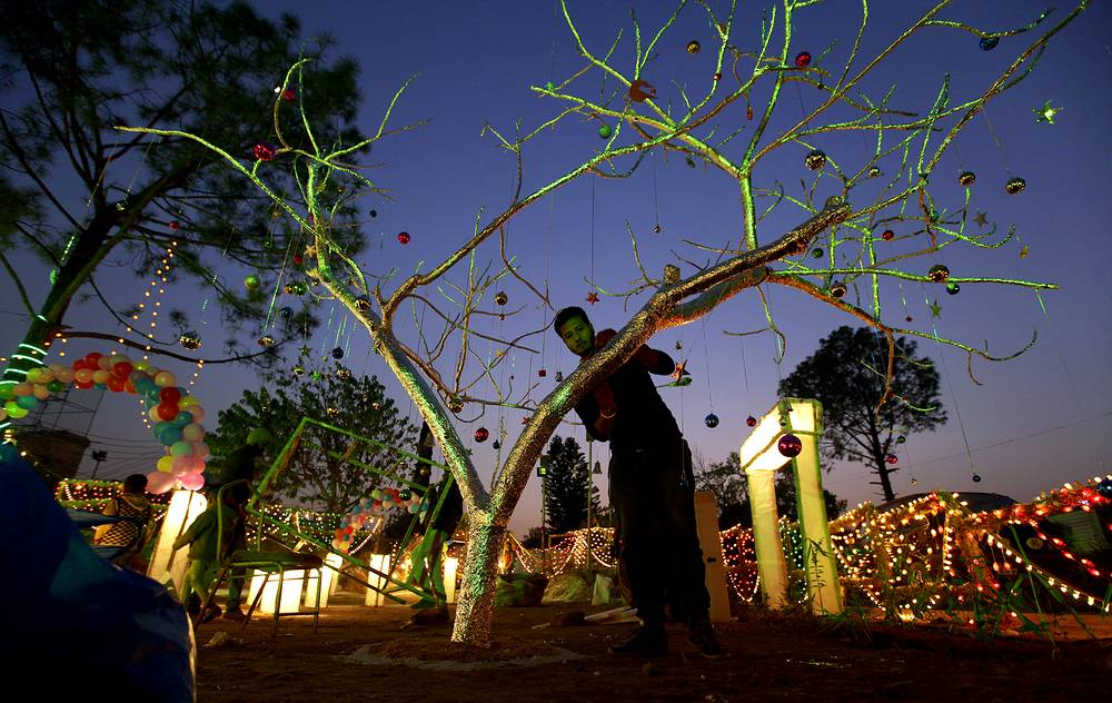 A man prepares a Christmas tree at an enclosure specially decorated for holiday celebrations, at a Christian neighborhood of Islamabad, Pakistan
