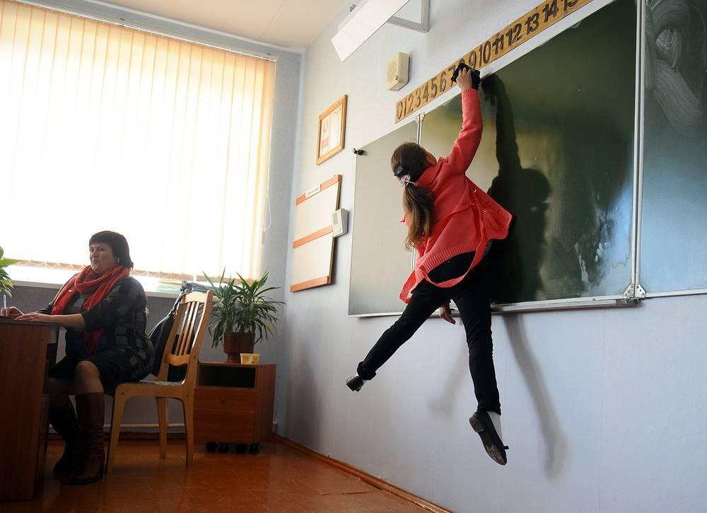 A girl washes the blackboard at the Kolno village school ahead of International Teachers' Day in Belarus, October 4