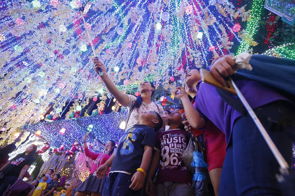 "Filipinos pose for souvenir shots at the ""Christmas House"" in suburban Cainta, Rizal province east of Manila, Philippines"