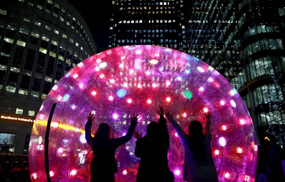 People interact with art installation Sonic Light Bubble at the Winter Lights festival at Canary Wharf in East London, Britain, January 16