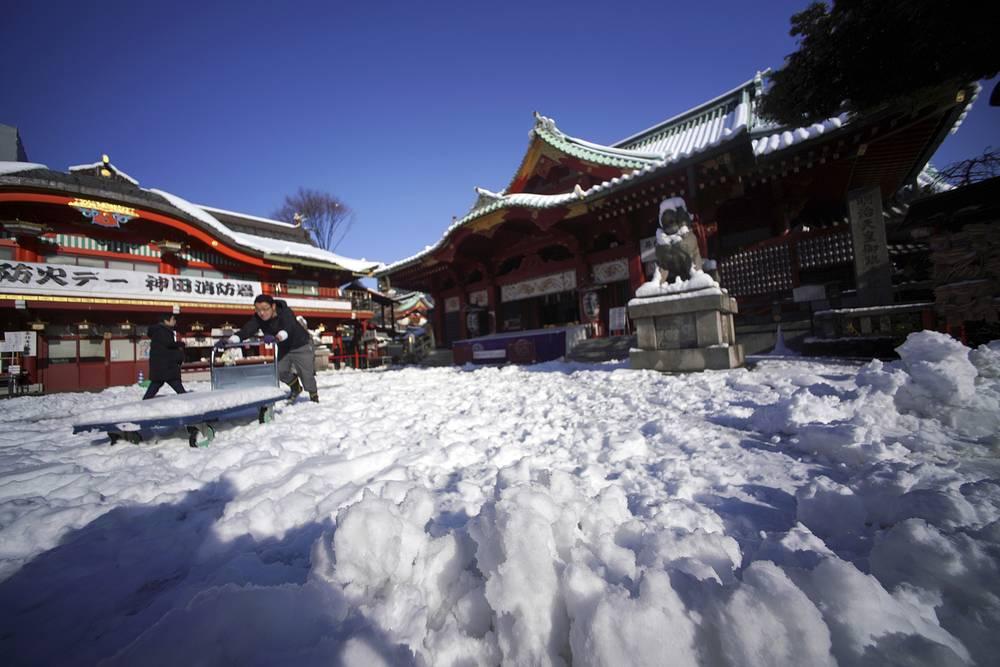 A man removes snow at Kanda Myojin shrine in Tokyo