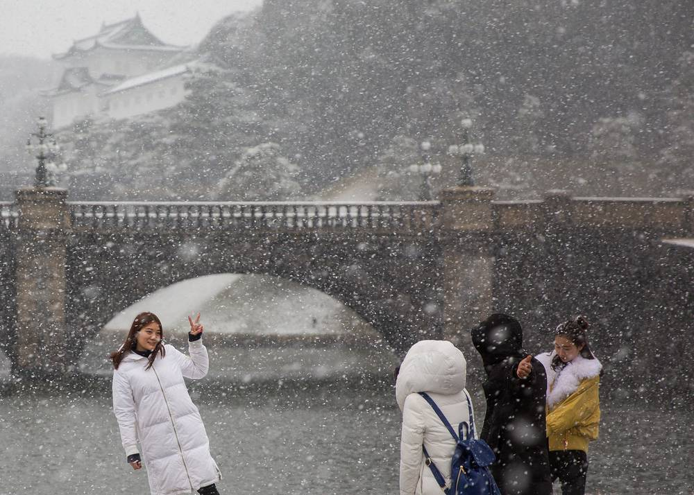 Visitors gather under a snow fall at the Imperial Palace in Tokyo, Japan