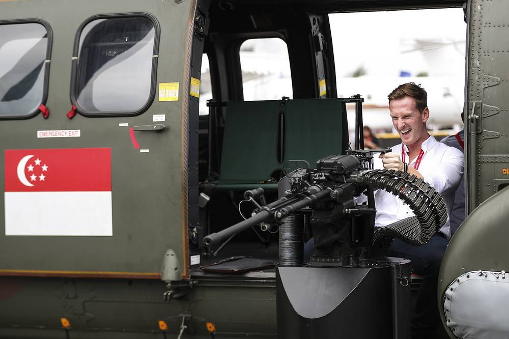 A visitor poses with the cabin-door machine gun of a Republic of Singapore Air Force Super Puma helicopter