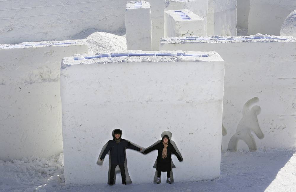 People pose in human body forms cut out of ice blocks as below freezing temperatures prevail, at the Pyeongchang Winter Festival, near the Olympic Stadium, Pyeongchang, South Korea, February 7