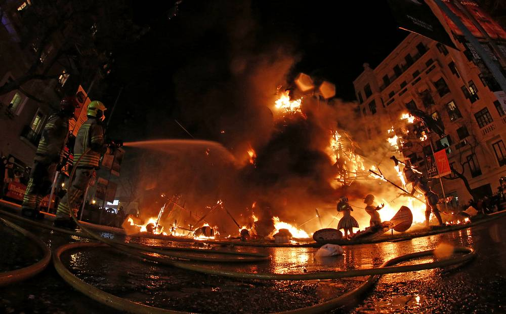 Firemen control the fire of burning satirical sculptures in Valencia