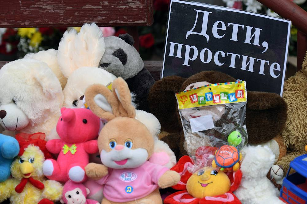 """Toys and a note reading """"Children, Forgive [Us]"""" outside the Zimnyaya Vishnya shopping centre in Kemerovo"""