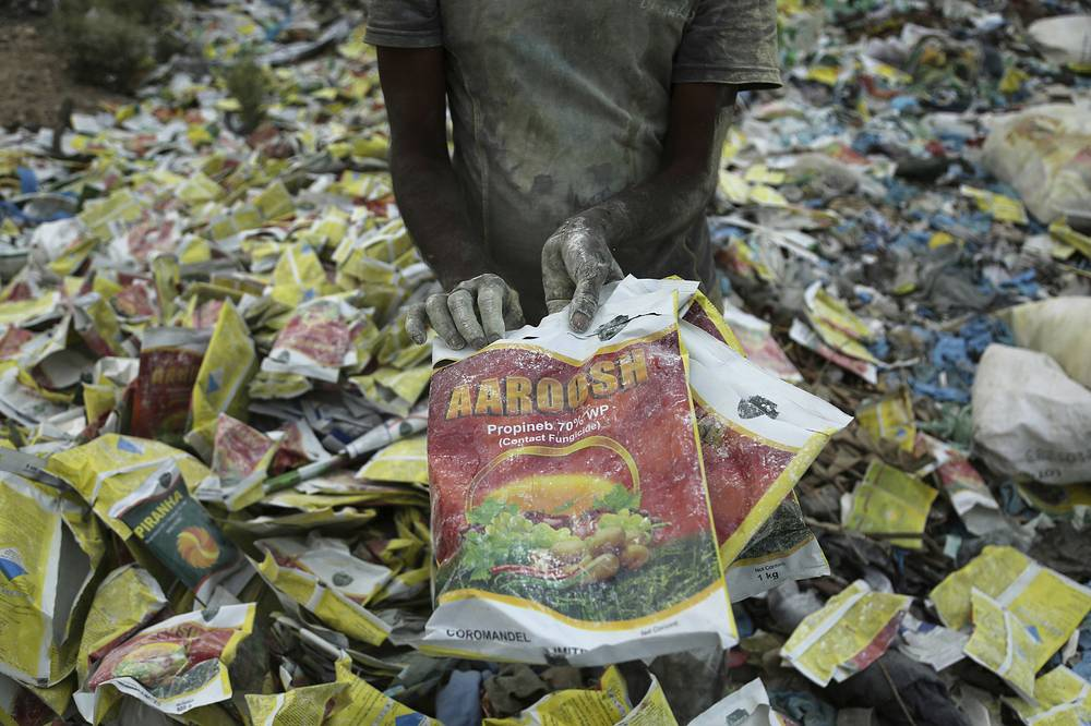 An Indian rag picker sorts plastic bags at an industrial area on the outskirts of Jammu, India