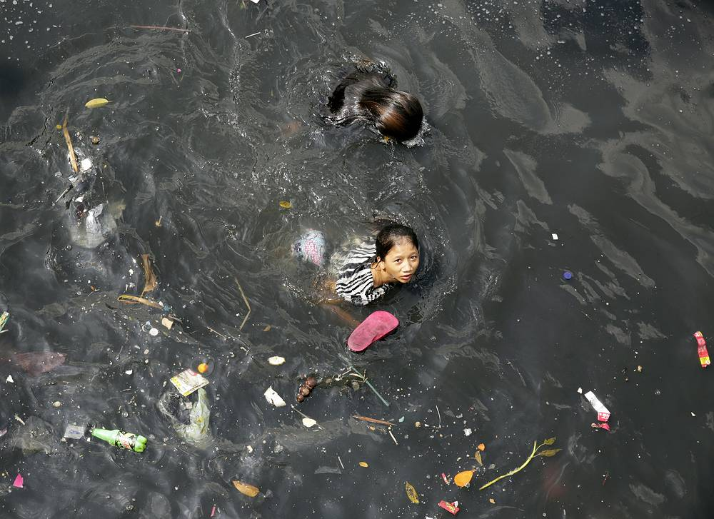 Filipino children frolic on the polluted water of Pasig river in Manila, Philippines. According to news reports, Pasig river is considered as the worst polluted river due to the large amount of wastes dumped into its water