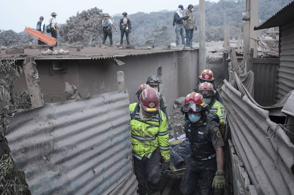 Firefighters remove a body recovered near the Volcan de Fuego in Guatemala