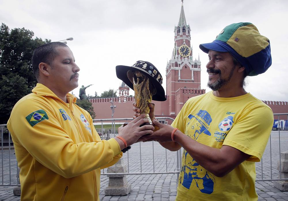 Brazilian fans hold a copy of the World Cup soccer tournament trophy near the Kremlin in Moscow