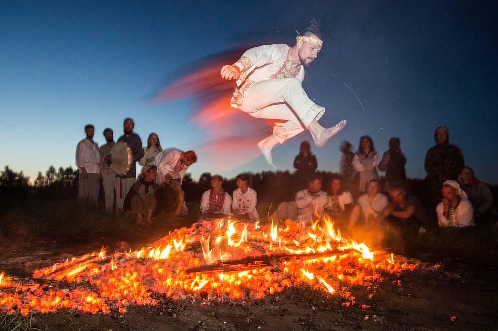 A man jumps over a bonfire during a summer solstice celebration in the village of Okunevo, June 24