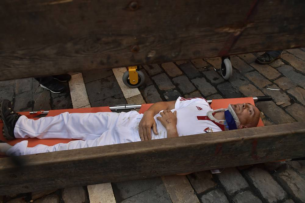 A reveller lies on a stretcher after getting hurt during the third day of the running of the bulls in Pamplona