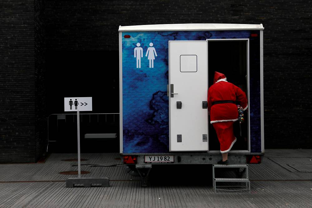 A person dressed as Santa Claus uses a restroom during the World Santa Claus Congress, an annual event held every summer in Copenhagen, July 23
