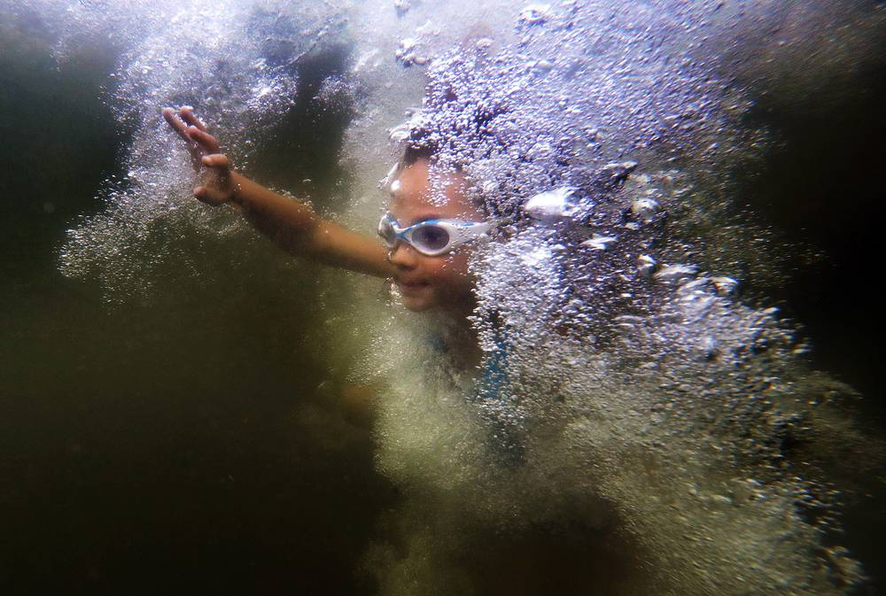 Eva Furman, 8, surfaces through a wall of bubbles after jumping from a small cliff into Lake Wood at Acadia National Park, USA, July 30