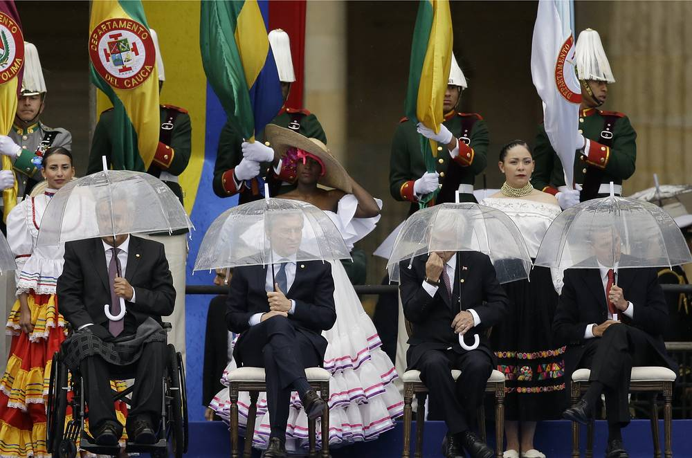 Ecuador's President Lenin Moreno, Argentina's President Mauricio Macri, Chile's President Sebastian Pinera and Mexico's President Enrique Pena Nieto hold umbrellas during the presidential inauguration ceremony for Ivan Duque, in Bogota, August 7